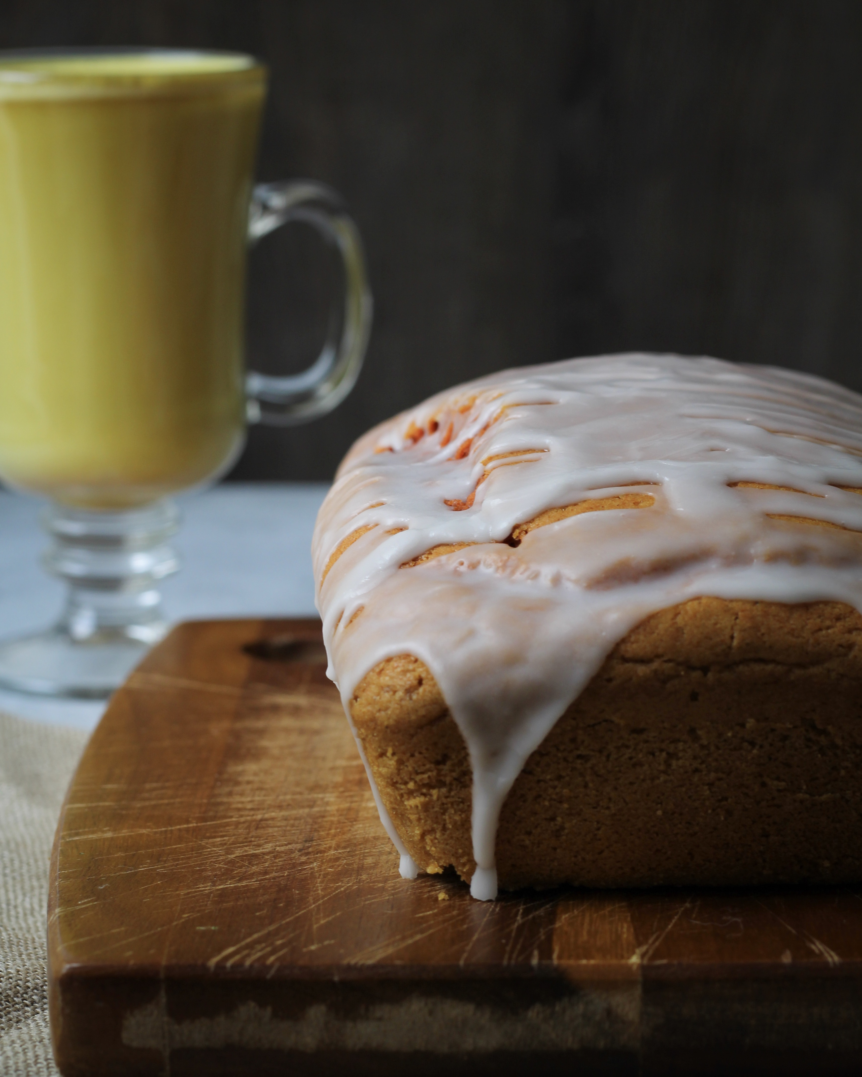 Golden Milk Loaf Cake (vegan) uncut with glass of golden milk behind